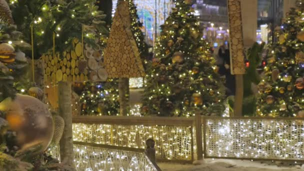 Christmas toys hanging on the branches of spruce. Festive decoration of the city. Out of focus festive lights. 4K