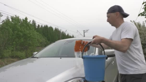 concentrated man washes modern grey hatchback with sponge