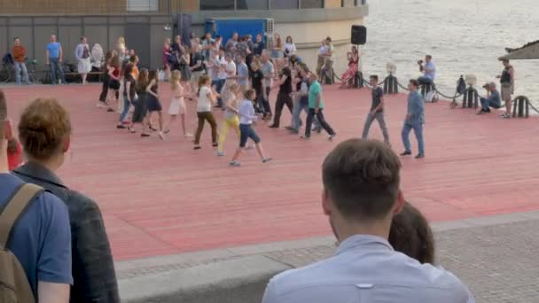 people dance at street party on city piers in early evening