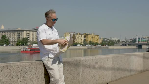 middle-aged man in a white shirt standing the waterfront pulls out a paper map