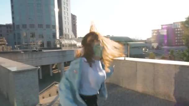 Braunhaarige Frau mit langen Haaren springt und tanzt im Hintergrund der Sonne