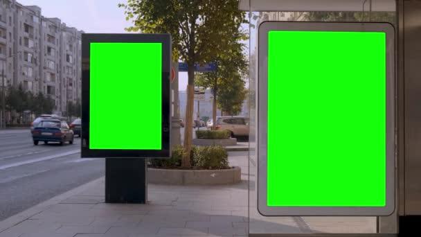 Dva billboardy na rušné ulici. Brzké ráno za slunečného dne