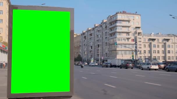 Zelená obrazovka billboard se nachází na ulici, kde auta jsou v pohybu