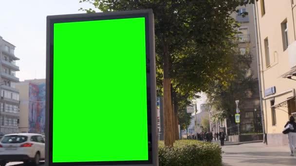 Billboard zelené obrazovky umístěný na rušné ulici.