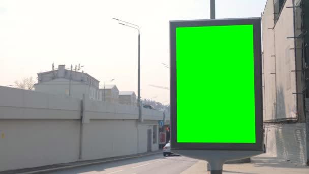 Egy hirdetőtábla zöld képernyővel az utcán. A közelben van egy híd az autóknak..