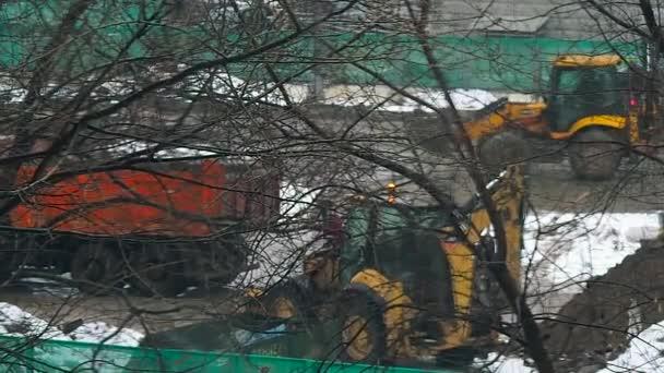 traktor betöltése a teherautó az építkezésen a téli