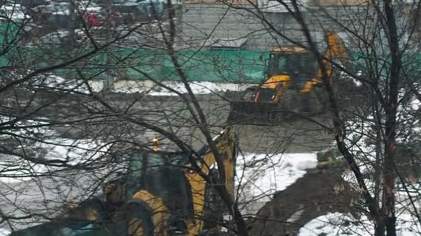 Kis exkavátor ás egy építkezésen a talaj télen hó alatt