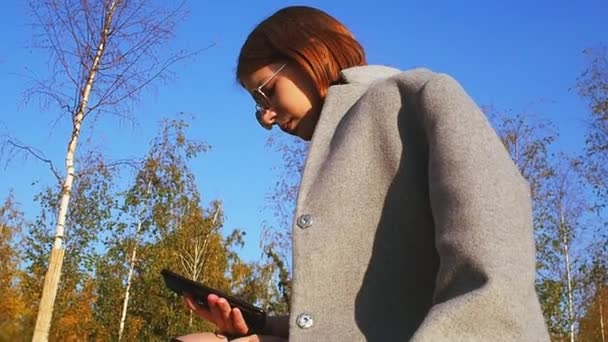 Teen girl in a gray coat and sunglasses is looking for something in her smartphone on a sunny day