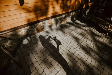 Shadow of saxophone player on stone pavement