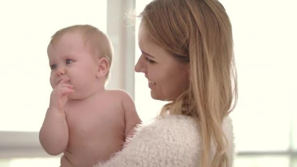 Smutné dítě na máminých rukou. Mladá matka drží dítě na objetí