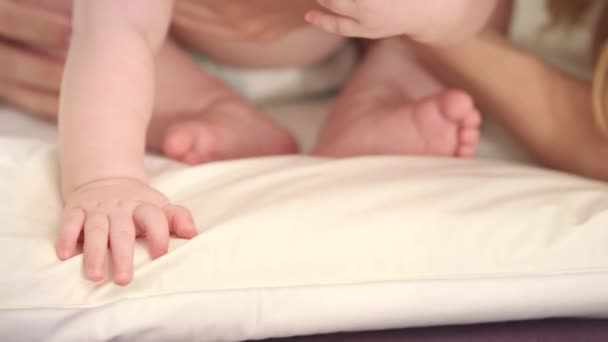 Little baby sitting in mother embrace. Baby in diapers eating green toy