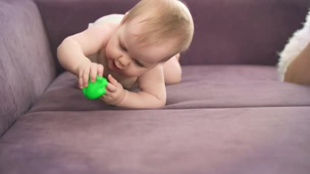 Adorable baby crawl on violet bed. Naked child in diapers gnawing toy