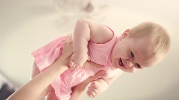 Šťastné dítě v rukou matka. Rozkošné dítě směje v rukou maminka