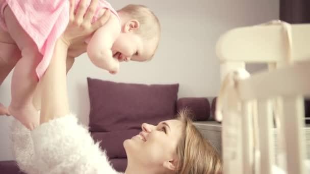Boldog anya fogja a babát a kezében. Imádnivaló kislány anyával élvezze az életet.