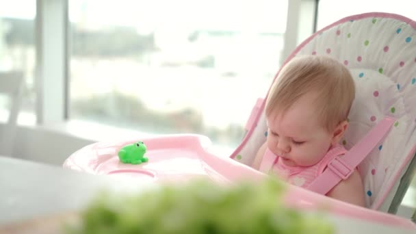 Beauty baby girl eating apple. Toddler missed food from hand. Baby fruit eating
