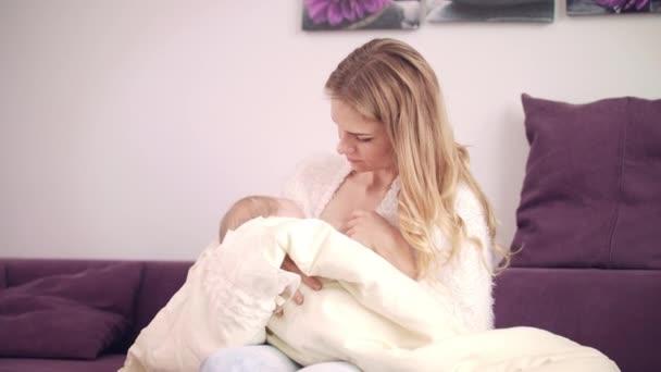 Krásná žena kojení doma. Péče o malé dítě