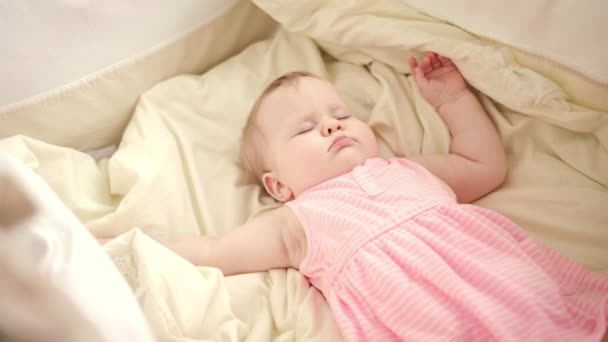Krásné dítě spát v postýlce. Matka rukama hladil spící dítě