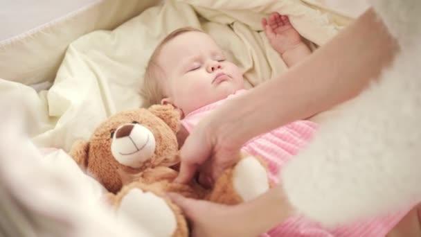 Matka a hračka pro spící dítě v postýlce. Rozkošné dítě spát v postýlce