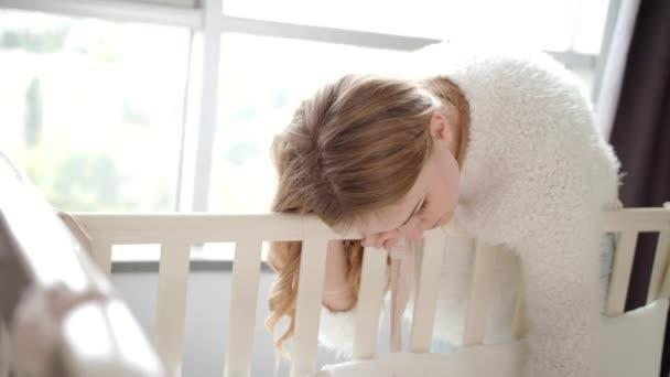 Šťastná matka poblíž postýlky. Máma dívá na spící dítě v postýlce