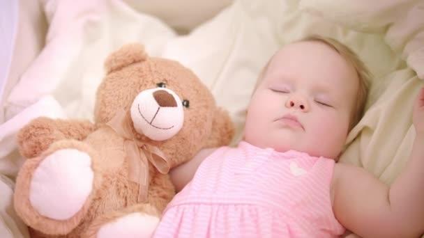 Malá holčička spí s hračkou v postýlce. Sladké spaní. Malá dívka sen v posteli
