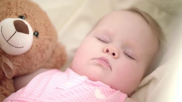 Rozkošné dítě spí v posteli. Portrét spící dítě s hračka medvěd