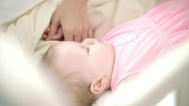 Malá holčička spí v posteli. Matka rukou hladila spící dítě