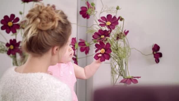 Rozkošné dítě dotýká květiny doma. Kluk jí krásné květiny do vázy