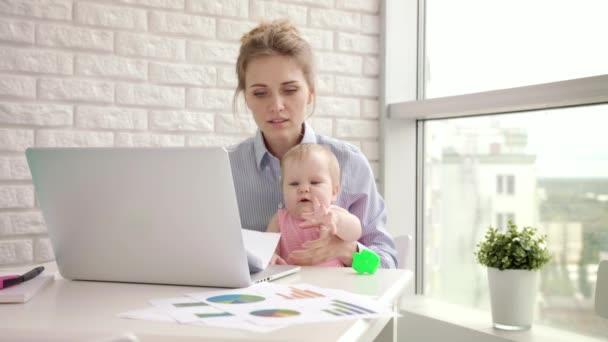 Frau mit Baby nicht konzentriert bei der Arbeit. Geschäftsmutter sucht Dokumente