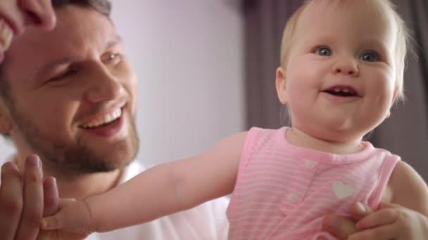 Rozkošná holčička v objetí, otec. Portrét dětské hry s mámou a tátou