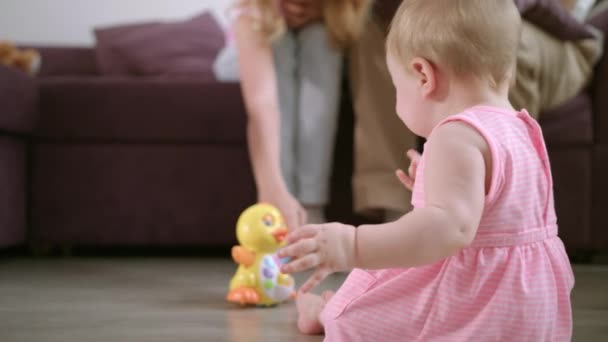 Infant playing with toy on floor. Sweet baby enjoy walking in room