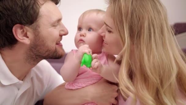 Šťastný matka s dítětem otec hospodářství na rukou. Máma a táta políbit dauther