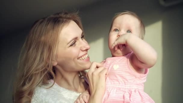 Happy mother holding baby girl on hands. Cheerful mom embrace toddler girl