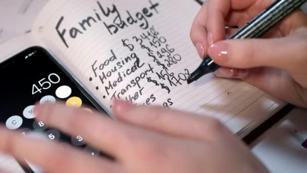 Žena vypočítat rodinný rozpočet na kalkulačku a psaní v poznámkovém bloku