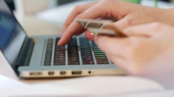 Frauenhände tippen Kreditkartennummer auf Laptop-Computertastatur