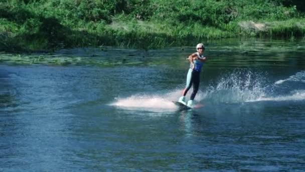 hübsches Mädchen beim Wakeboarden auf dem Sommerfluss. Frau übt sich im Wasserski