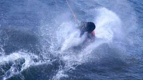 Extrémní muž studovat na koni wakeboarding kousek na vodě. Extrémní vodní sporty