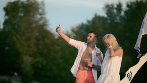 schöne Liebende beim Selfie mit dem Smartphone. Liebespaar macht Foto bei Sonnenuntergang. gemeinsam glückliche Momente festzuhalten. Junge Leute halten Champagnergläser in der Hand und blicken in die Kamera