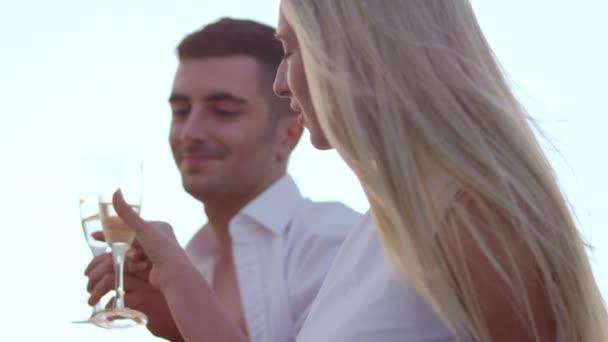 Das modische junge Paar trinkt Champagner bei Sonnenuntergang. Glückliche Menschen feiern