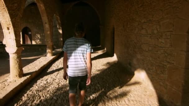 Hombre moderno camina entre cuarto oscuro antiguo en cámara lenta ...