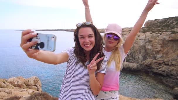 Beautiful girls taking selfie photo on mobile phone at sea beach. Woman selfie