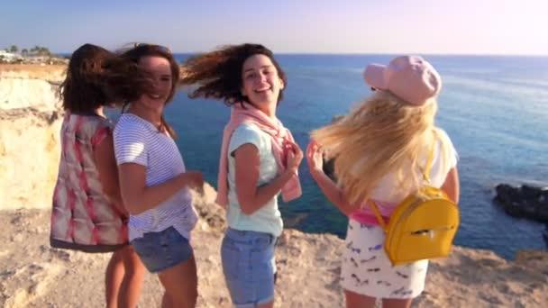 Happy woman waving hands on rocky seashore. Female friends having fun