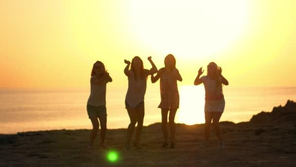 Summer woman jumping silhouettes at beach sunset. Playful girls enjoy sea sunset