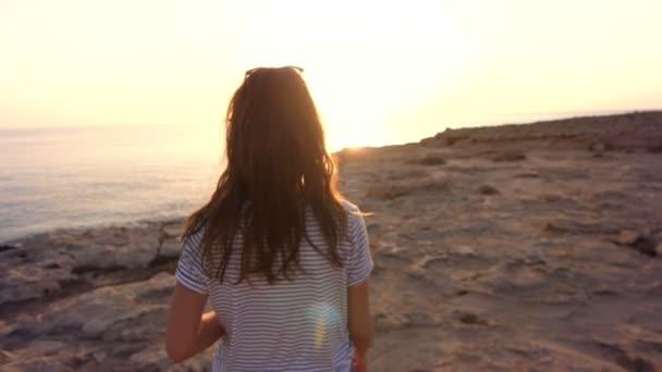 Žena běží na skalnaté pláži zpět zobrazení. Krásná dívka si večerní slunce