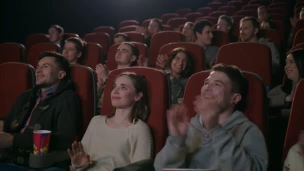 Lustige Zuschauer applaudieren im Theater. Menschen klatschen im Theater in die Hände