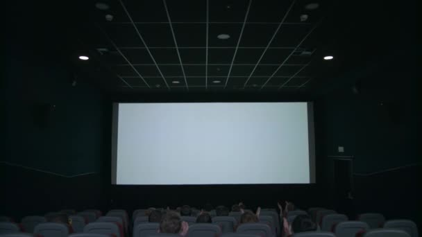 Spectators sitting in front of white screen. People applauding in cinema