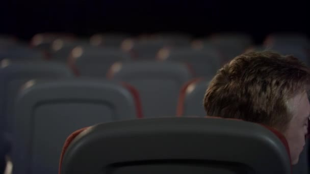 Loving couple kissing in back seats in cinema in slow motion.