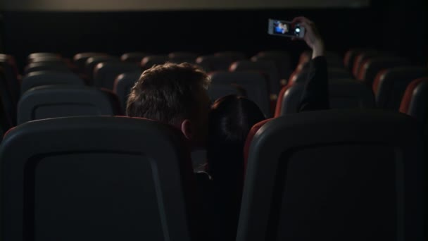 Young people kissing in empty cinema hall. Love couple making selfie photo