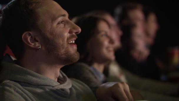 Fiatal srác a fülébe, nevetve a film nézése közben pattogatott kukoricát eszik fülbevalóval
