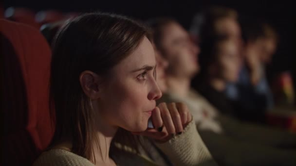 Concentrated girl watching thrilling movie at cinema. Enjoy cinema concept