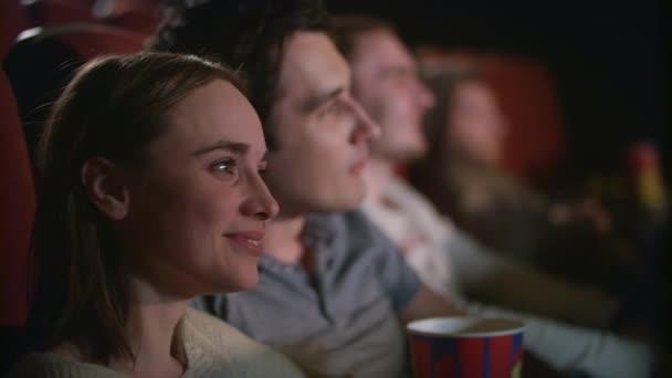 People in auditorium watching film. Joyful young people in cinema